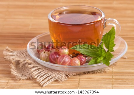 Fruit tea(tea package) in cup with gooseberry - stock photo
