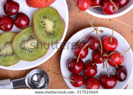 fruit with cherry, strawberry, kiwi on wooden plate - stock photo