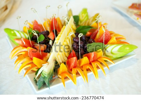 fruit with wooden skewers on a plate - stock photo