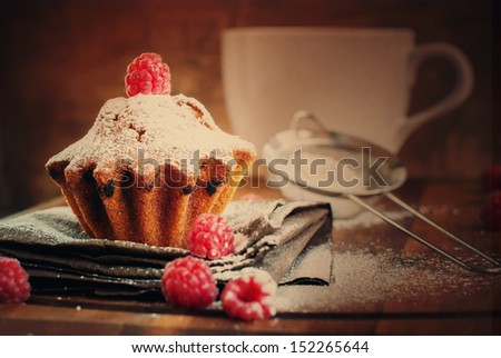 Fruitcake Decorated with Raspberry and icing sugar at the wooden table, tonal - stock photo