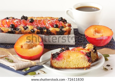 Fruitcake with plums and a cup of black coffee.