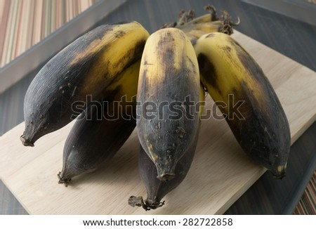 Fruits, A Bunch of Black Rotten Wild Banana, Asian Banana or Cultivated Banana on A Wooden Cutting Board. - stock photo