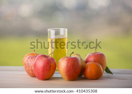fruits and apple juice on a wooden table, outdoor