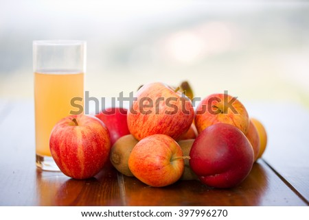fruits and juice on a wooden table, outdoor - stock photo