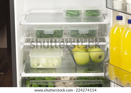 Fruits and vegetables in two containers in a modern fridge - a healthy food concept. - stock photo
