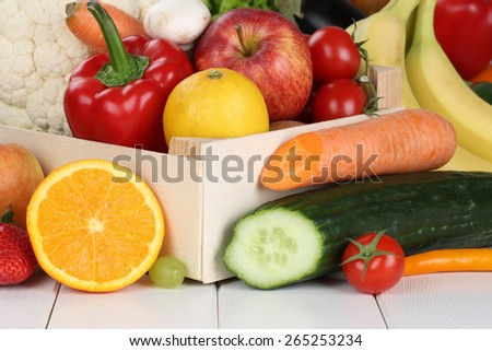 Fruits and vegetables like oranges, apple, tomatoes, banana in wooden box - stock photo