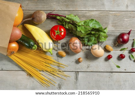fruits and vegetables rolling from paper bag on weathered wooden table - stock photo