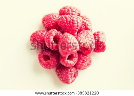 fruits, berries, diet, eco food and objects concept - juicy fresh ripe red raspberries on white - stock photo