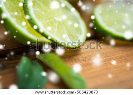 fruits, citrus, detox, diet and objects concept - close up of lime slices on wooden table over snow