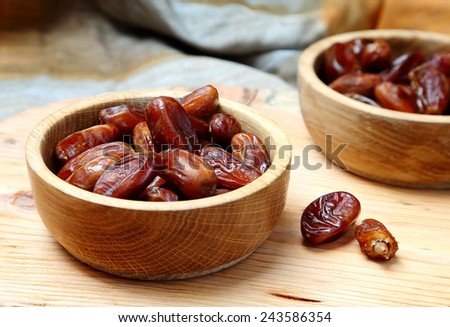 Fruits dates in wooden bowl closeup on  table - stock photo