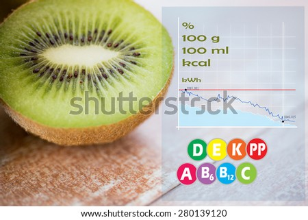 fruits, diet, food and objects concept - close up of ripe kiwi slice on table with calories and vitamin chart - stock photo