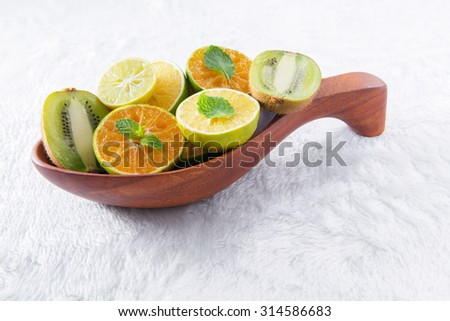 Fruits in a wooden basket on white background