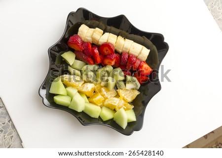 Fruits in black ceramic plate - stock photo