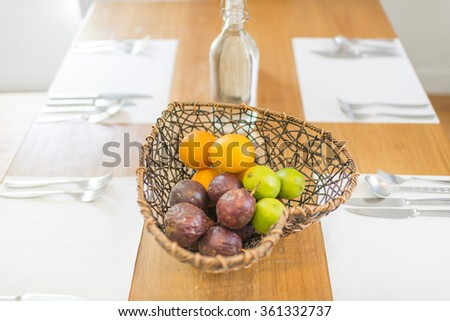 Fruits in heart shape basket on dining table with dishware on white napkin