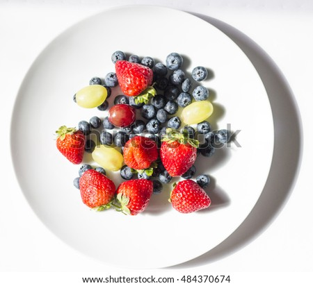 Fruits including strawberries, blueberries and grapes fresh from a farm in a white plate on a balcony in a sunny morning with happy mood