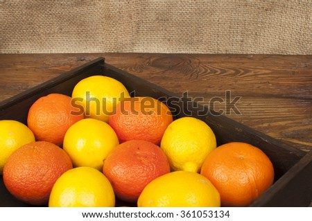 fruits: lemons and oranges on a wooden table - stock photo