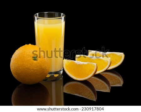 Fruits of a ripe orange and juice in a high glass on a black background - stock photo