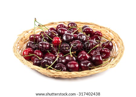 Fruits of sweet cherries in a wicker plate isolated on white background.