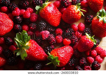 Fruits of the forest: strawberries, raspberries and blackberries against wooden background.. Healthy breakfast food. - stock photo