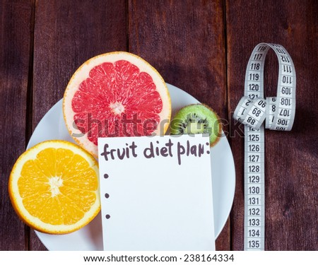 Fruits on a white plate and measuring tape. The concept of diet plan, healthy lifestyle and weight loss. The fight against excess weight. Low-fat diet. - stock photo