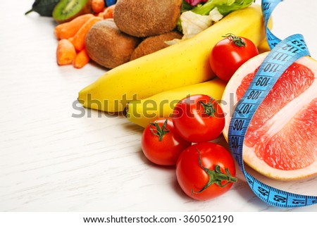 Fruits, vegetables and measuring tape on light wooden background. healthy eating concept.  - stock photo