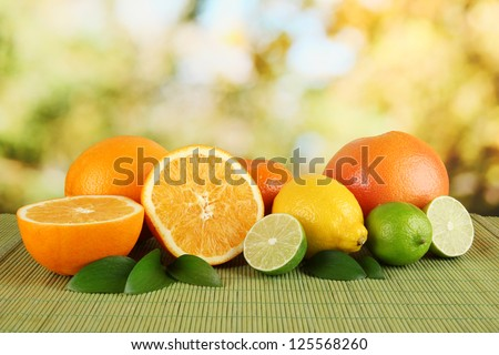 Fruits with leafs on table on bright background - stock photo
