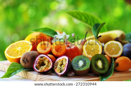 Fruits with leafs on table on green background - stock photo