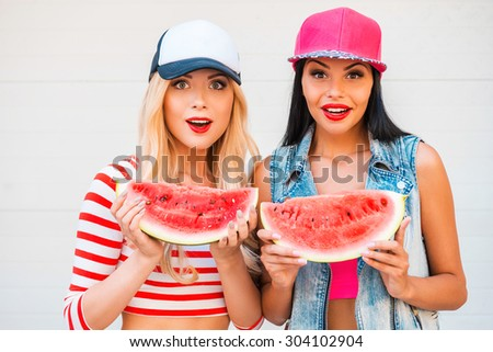 Fruity fun. Two surprised young women holding slices of watermelon and staring at camera while standing outdoors - stock photo