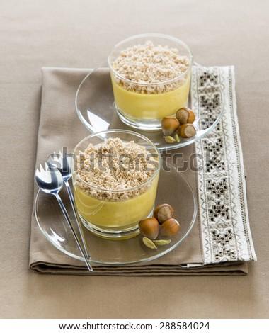 fruity mango cream with turmeric cardamom sprinkled with hazelnut in glass cups - stock photo