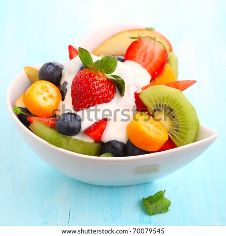 Fruity summer salad in white bowl with yogurt - stock photo