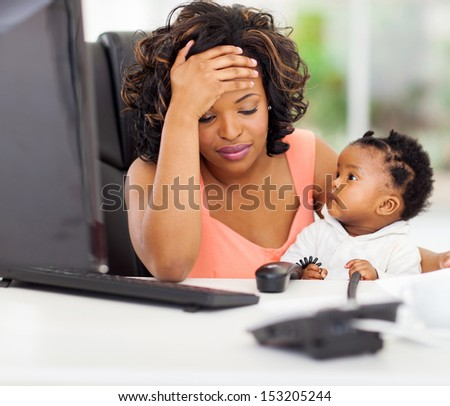 frustrated african american businesswoman with her little baby in office - stock photo