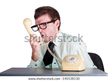 Frustrated and angry businessman sitting at desk shouting down the line of retro telephone receiver. Staff discipline concept - stock photo