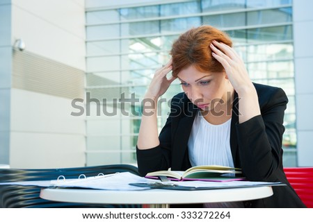Frustrated and tired business woman sitting in modern background