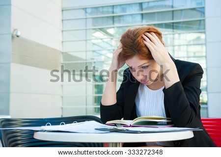 Frustrated and tired business woman sitting in modern background - stock photo