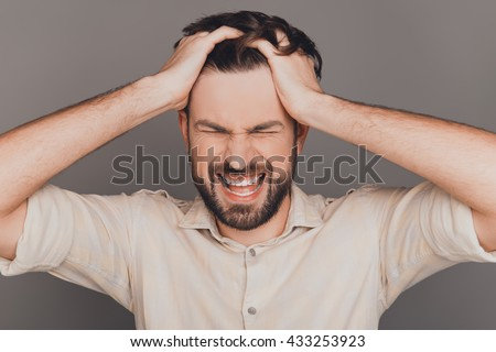 Frustrated angry man with big problems yelling and touching head