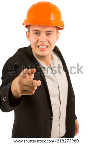 Frustrated angry young architect or engineer in a suit and hardhat gnashing his teeth in anger and pointing at the camera, upper body on white - stock photo