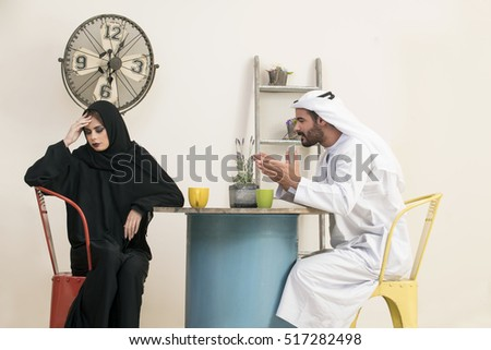 Frustrated Arabian couple sitting in a vintage interior , Arabian couple not talking after a fight in a vintage restaurant, bad relation concept