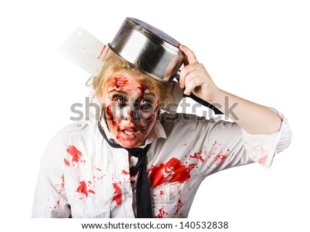 Frustrated blond woman with pan on her head having had an accident making strawberry jam which is now covering her face and shirt - stock photo