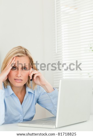 Frustrated blonde businesswoman sitting in front of her notebook on the phone looking  into the camera in her office