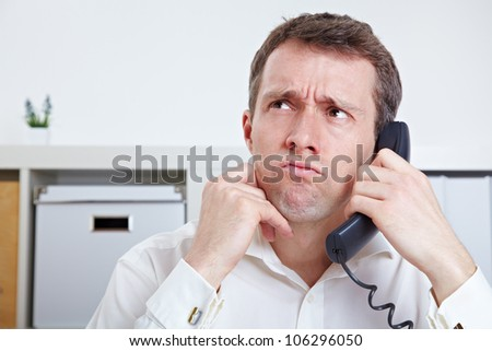 Frustrated business man on the phone in waiting queue - stock photo