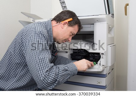 Frustrated business man opening photocopy machine in office trying to fix problem