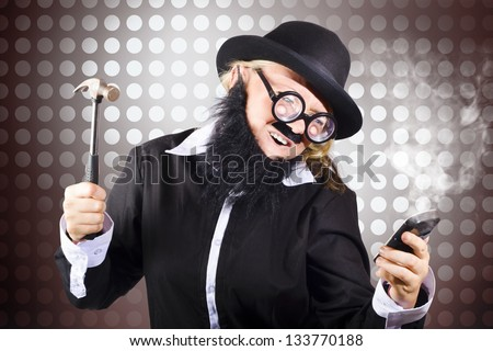 Frustrated business man smashing a smart mobile phone with hammer in a technology failure concept