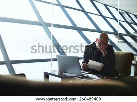 Frustrated business man surrounded by paperwork sitting in office interior with hand on his face, examining paperwork businessman looking so tired, flare light from the window - stock photo