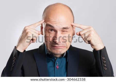 Frustrated business man with a headache. isolated over gray - stock photo