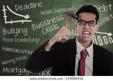 Frustrated businessman hitting his head with hammer - stock photo