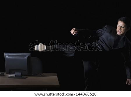 Frustrated businessman kicking a desktop pc - stock photo