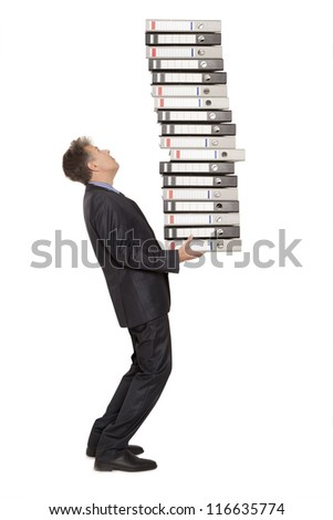 Frustrated businessman looking at pile of file folders - stock photo