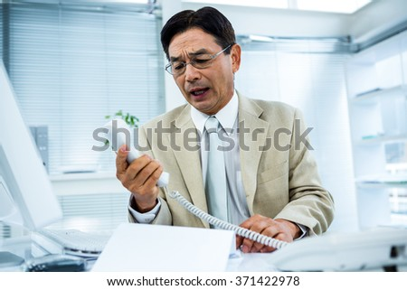 Frustrated businessman looks his phone in his office - stock photo