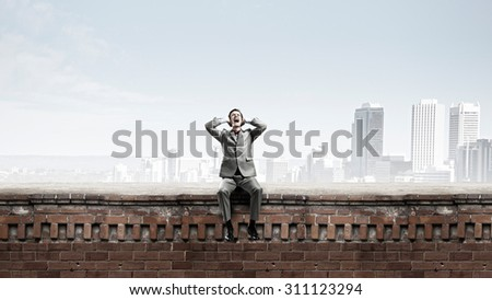 Frustrated businessman on building top closing ears with hands - stock photo