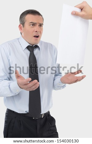 Frustrated businessman. Shocked middle aged businessman gesturing while looking at the document - stock photo